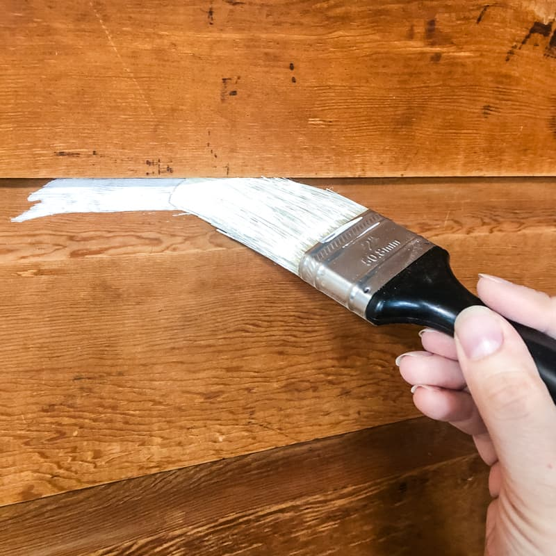 applying shellac-based primer to wood paneling with a paint brush