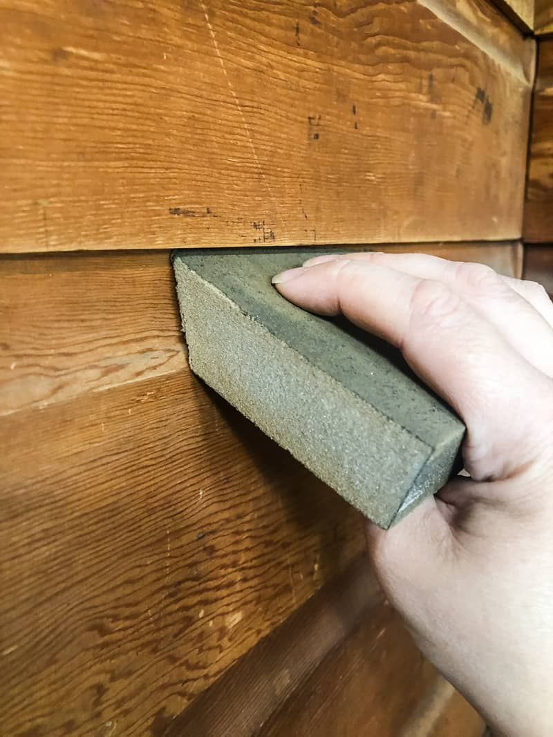 sanding wood paneling with angled edge of a sanding sponge