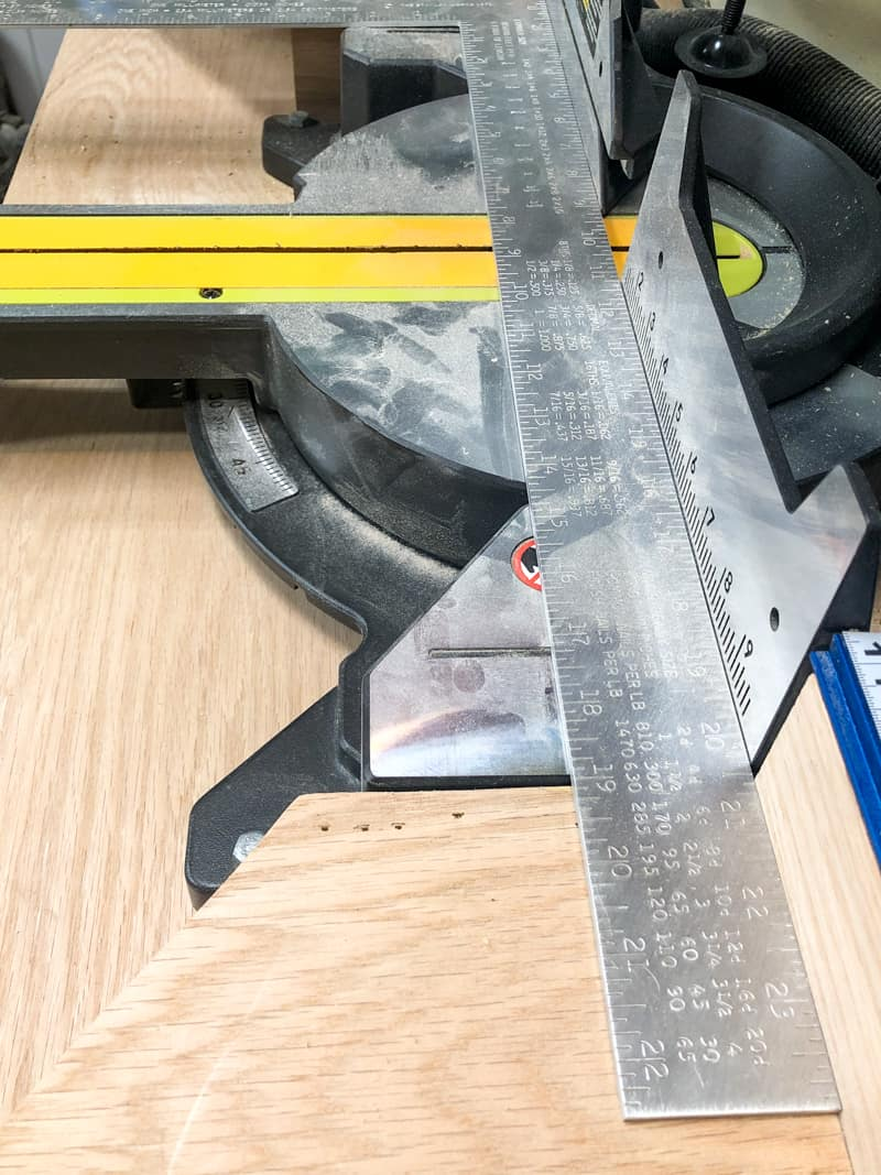 metal ruler on miter saw base to check fence