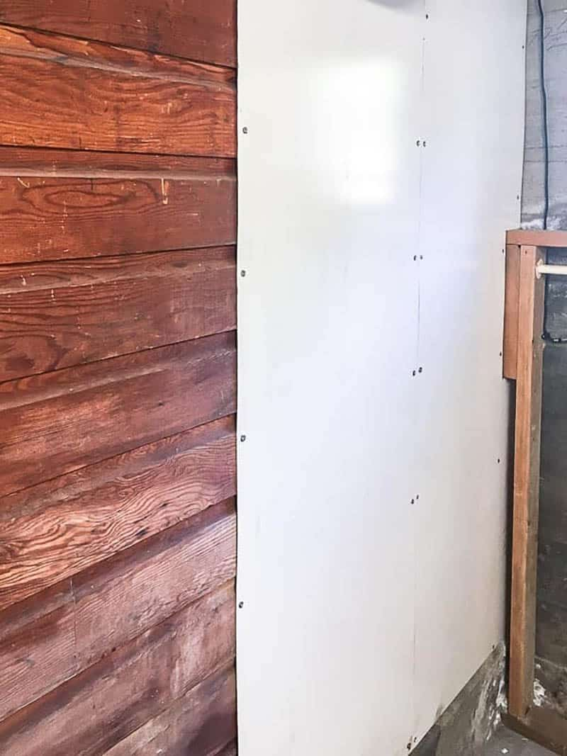 wood paneled wall covered with white board on half