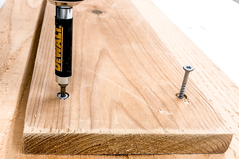 screwing countersink screws into bottom board of deck rail table