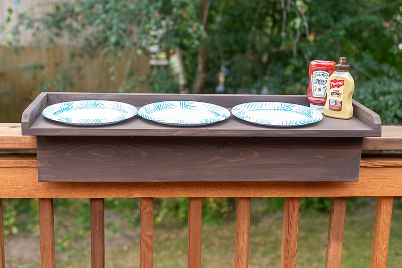 deck railing table with three paper plates and condiments