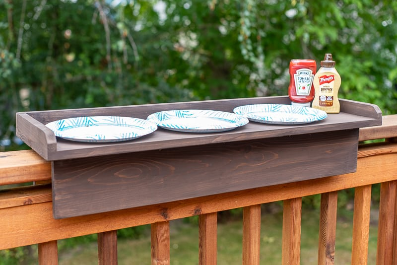 DIY balcony railing table with three plates, ketchup and mustard next to the grill