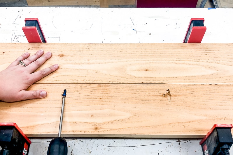 screwing together both sides of the deck railing table with pocket hole screws