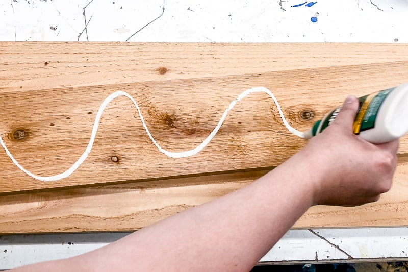 applying exterior wood glue to underside of center board of balcony railing table before screwing it into place