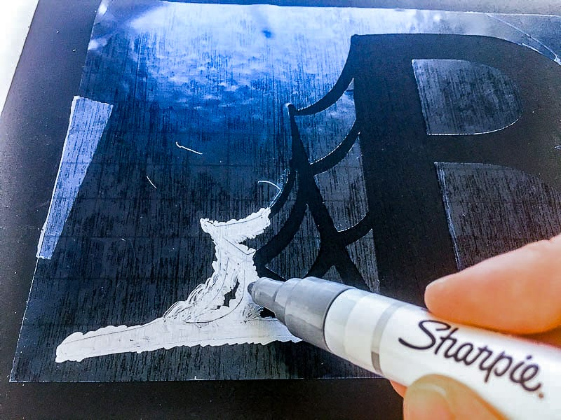 applying silver paint to spider stencil