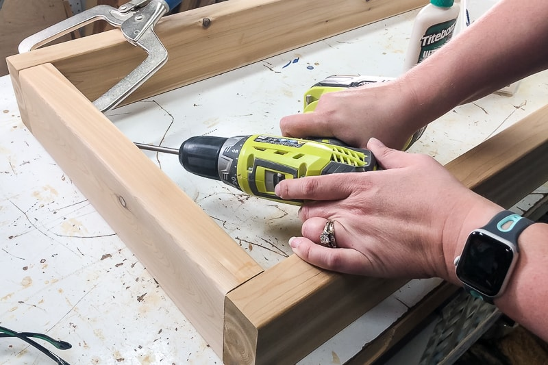 screwing frame of DIY outdoor coffee table together with right angle clamp