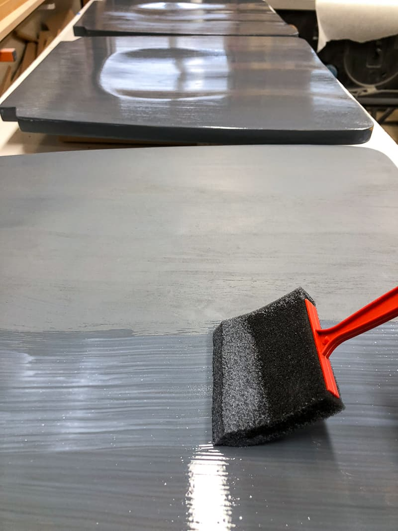 applying top coat to refinished chairs with a foam brush