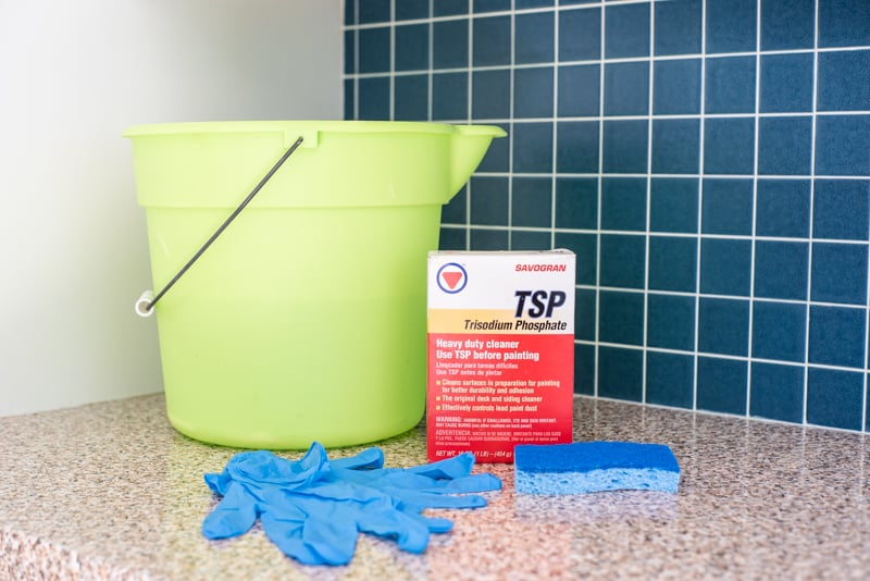 green bucket, TSP, sponge and gloves on kitchen counter for cleaning before painting tile backsplash