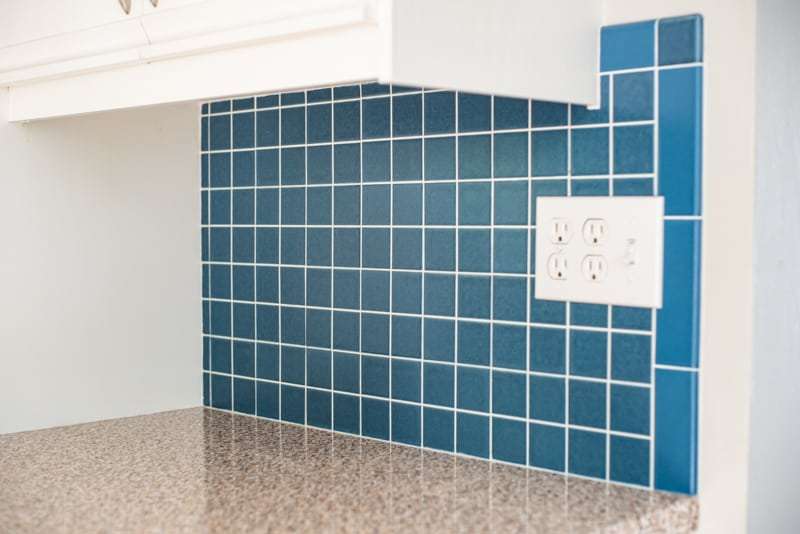 blue tile backsplash in kitchen with white cabinets and brown granite countertops