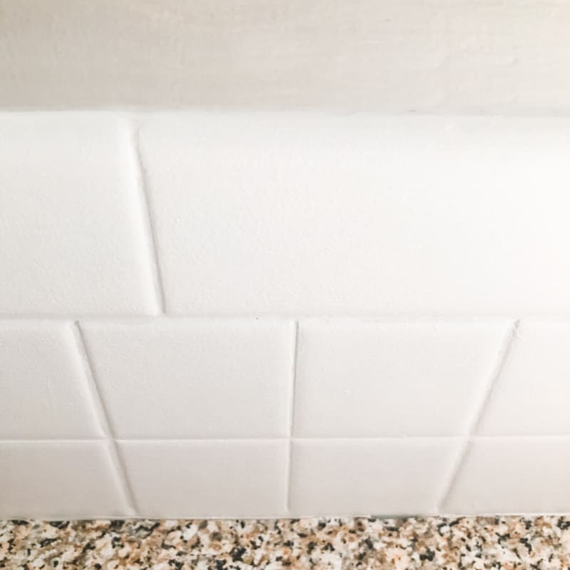 Caulked seam between painted tile backsplash and the wall