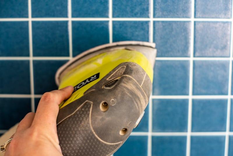 sanding backsplash tile before painting with a Ryobi corner cat sander