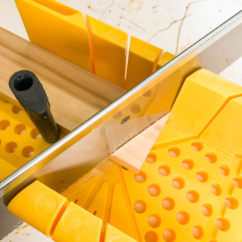 cutting bottom of DIY blanket ladder at an angle with a miter box