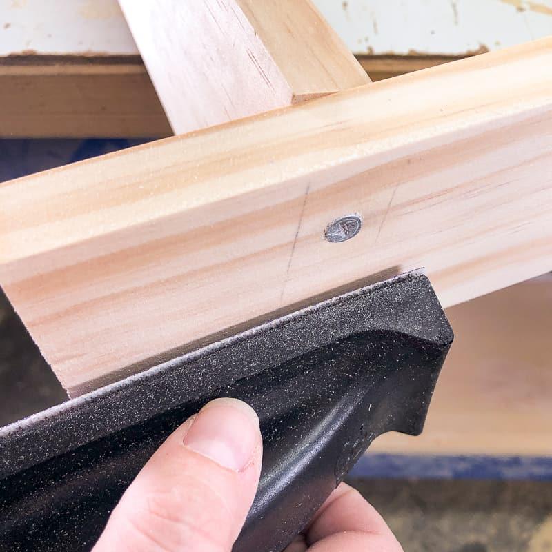 sanding off pencil marks from side of DIY blanket ladder