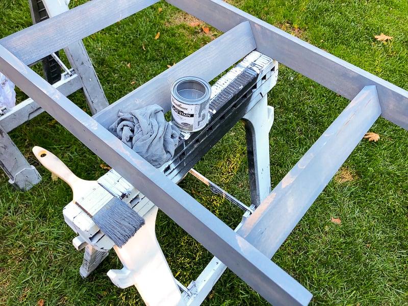 applying grey stain to DIY blanket ladder