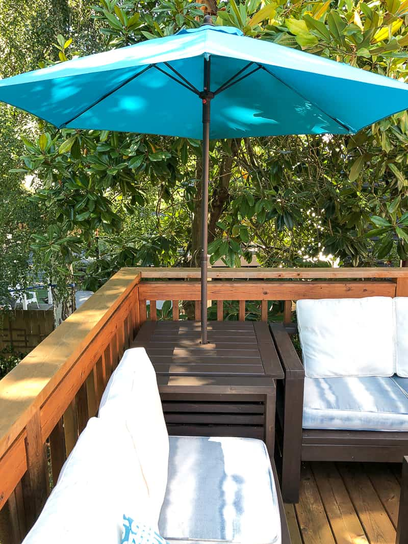 umbrella stand table in corner between two outdoor sofas
