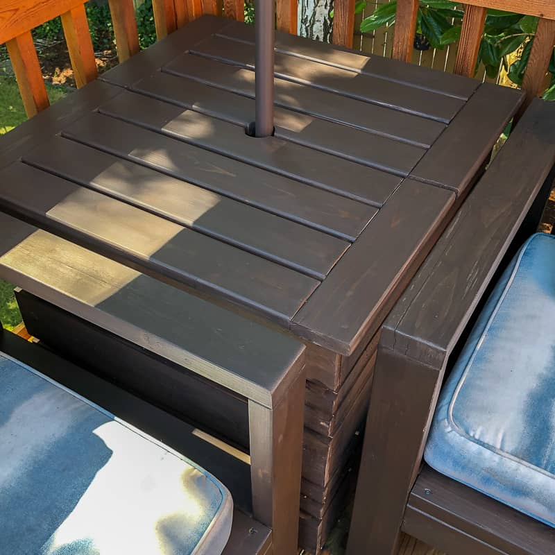 umbrella stand table in corner of deck between two outdoor sofas