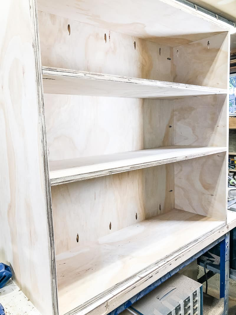 three shelves on one side of the DIY workbench installed