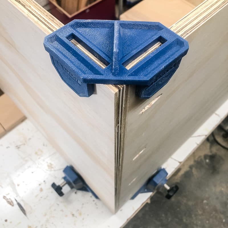corner clamps holding plywood pieces of DIY workbench together
