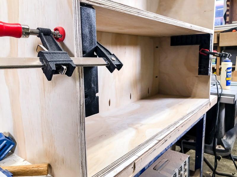 first shelf of DIY workbench being installed