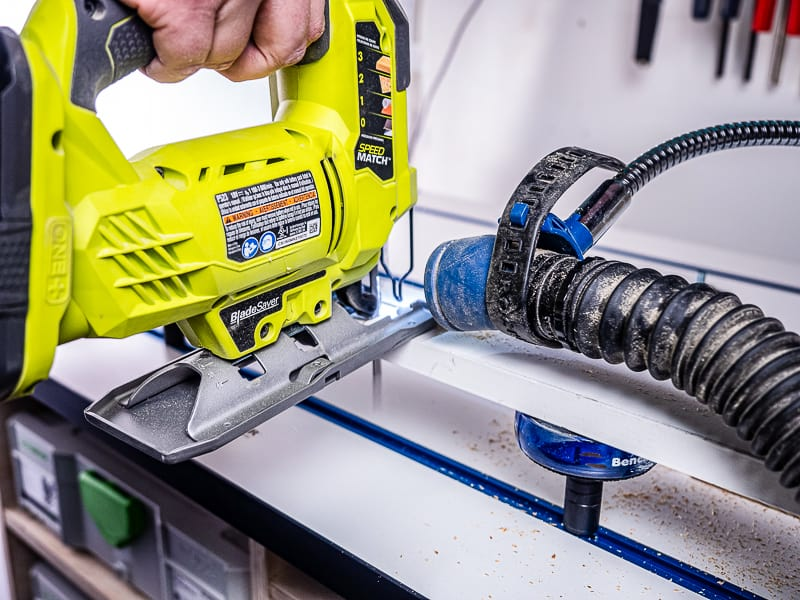 cutting with jigsaw on workbench with dust collector hose