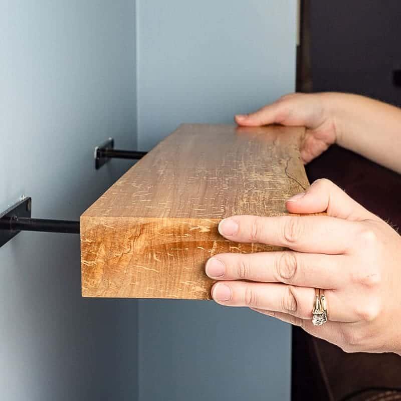 sliding live edge floating shelves onto brackets