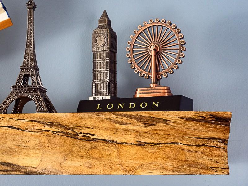 travel souvenirs on live edge floating shelf