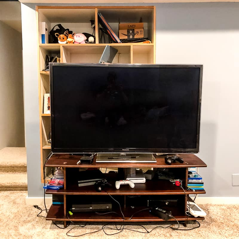 flat screen tv on stand in front of built in entertainment center