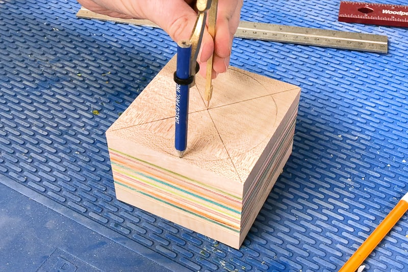 drawing a circle with a compass on a block of wood