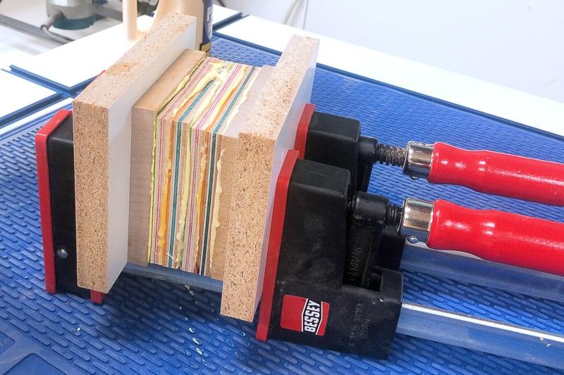 layers of skateboard veneer in parallel clamps