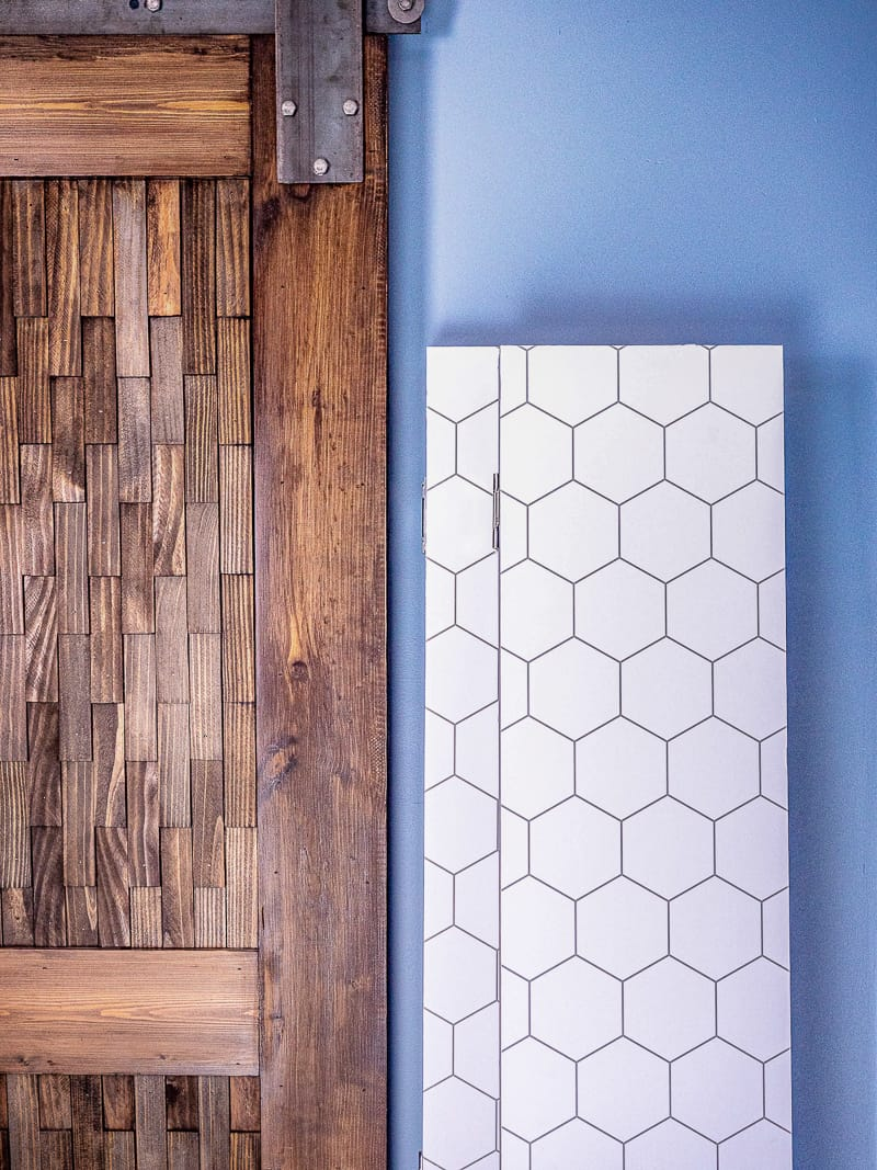 DIY room dividers folded up and leaning against the wall next to a sliding barn door