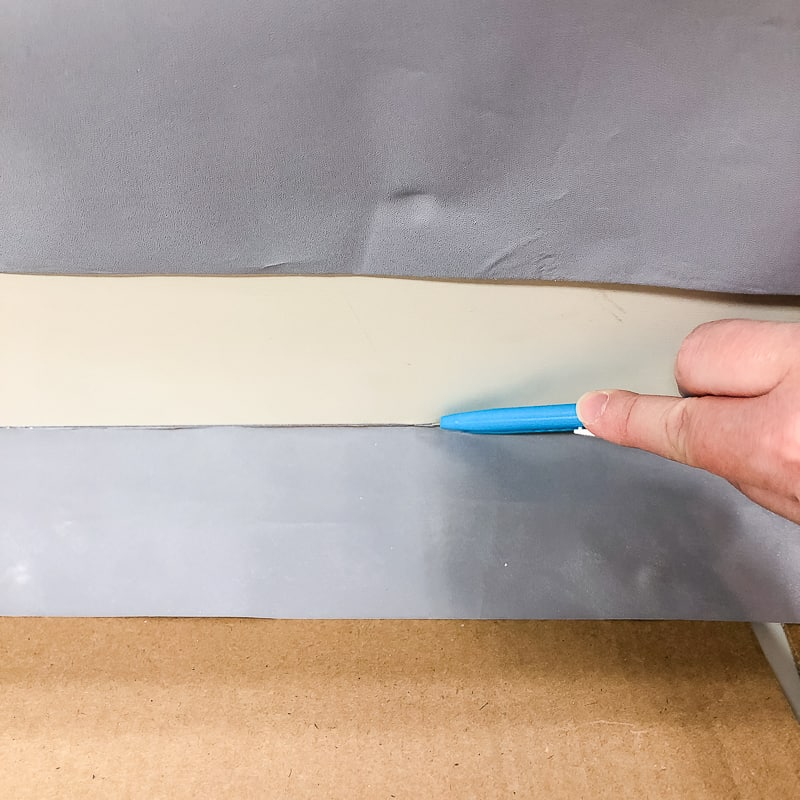 cutting away excess contact paper with a razor blade