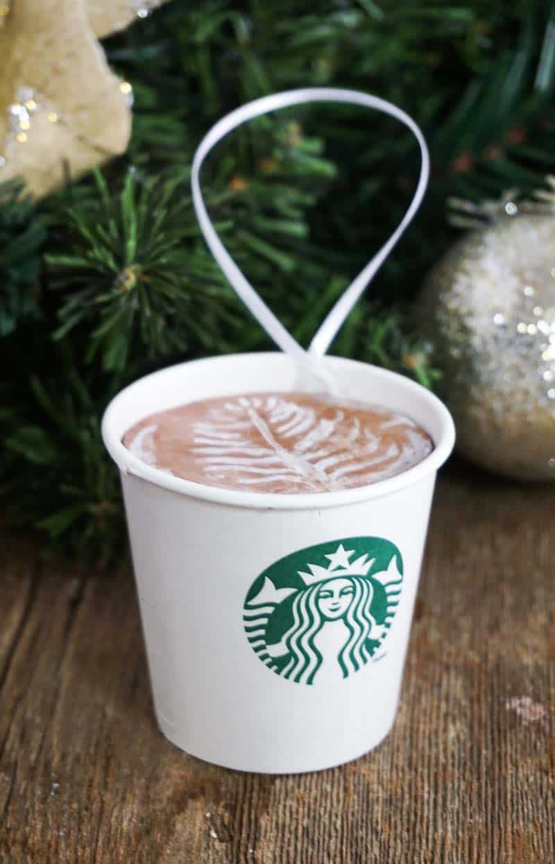 DIY Starbucks latte ornament on table with Christmas decor in background