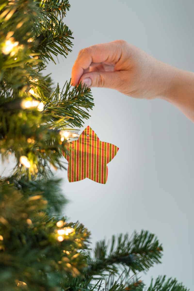 star shaped wooden ornament being hung from the Christmas tree