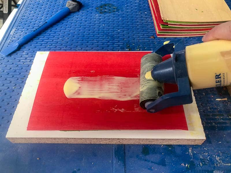 applying wood glue with a roller onto red dyed veneer