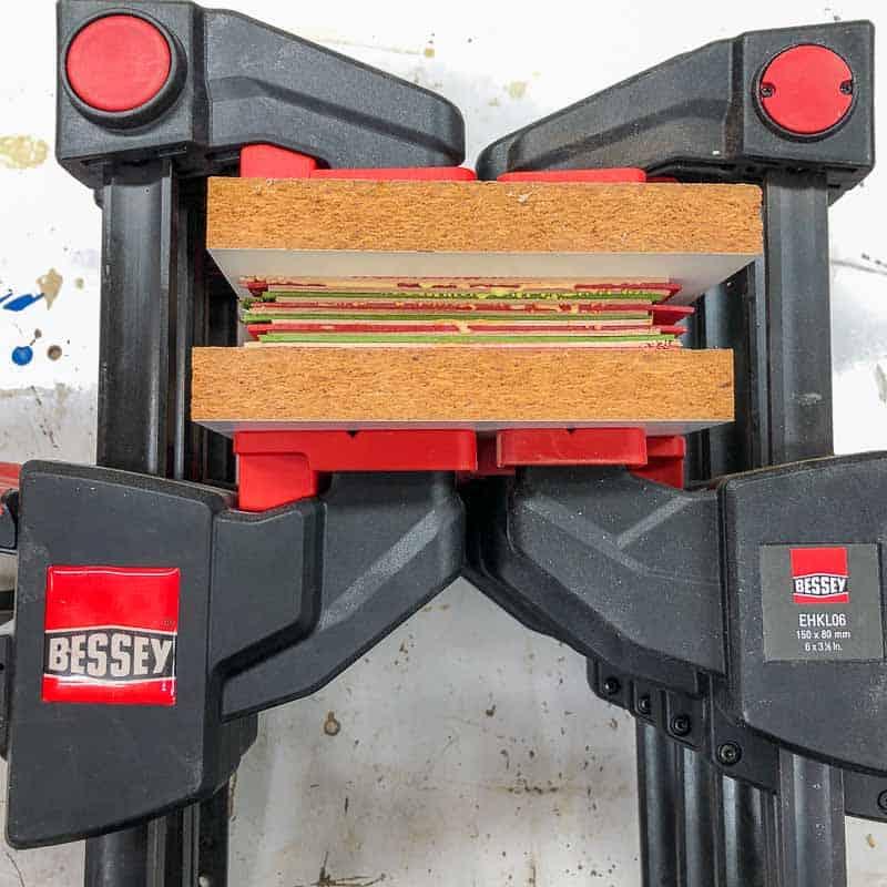 layers of dyed veneer clamped between melamine boards