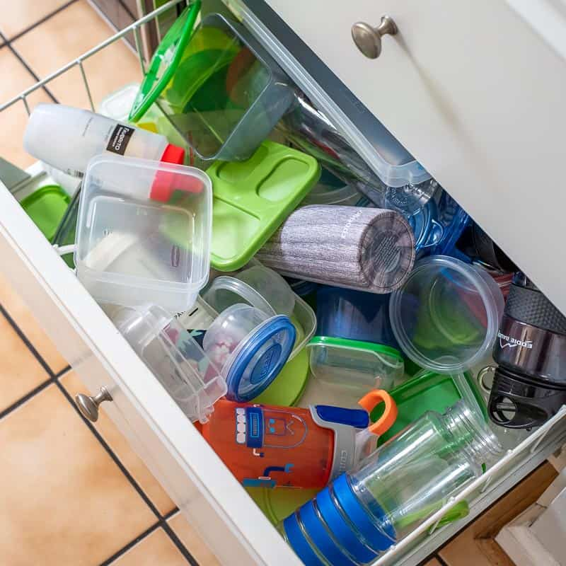 kitchen drawer with a mess of plastic containers