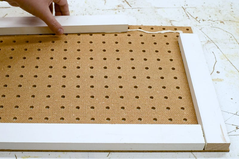 applying scrap wood to perimeter of pegboard