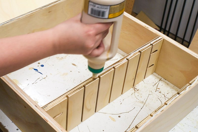 applying wood glue to bottom of the DIY drawer organizer
