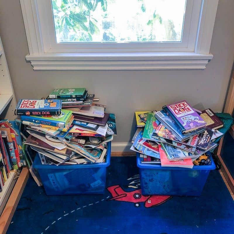 blue rolling plastic bins overflowing with books under window in kids room