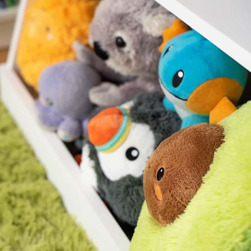 stuffed animals in bottom bin of DIY kids bookshelf with toy storage