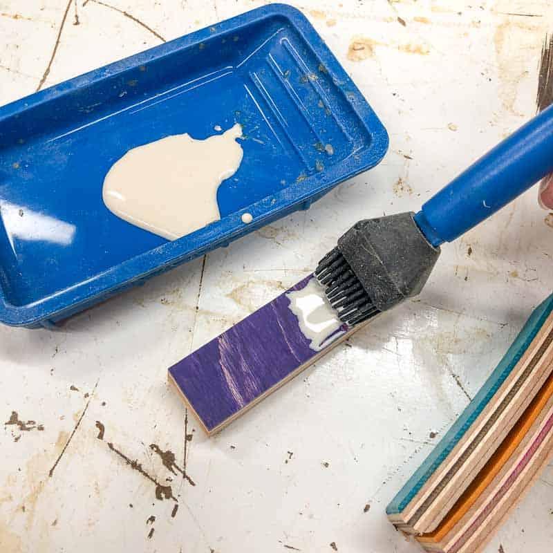 applying wood glue to skateboard wood strips