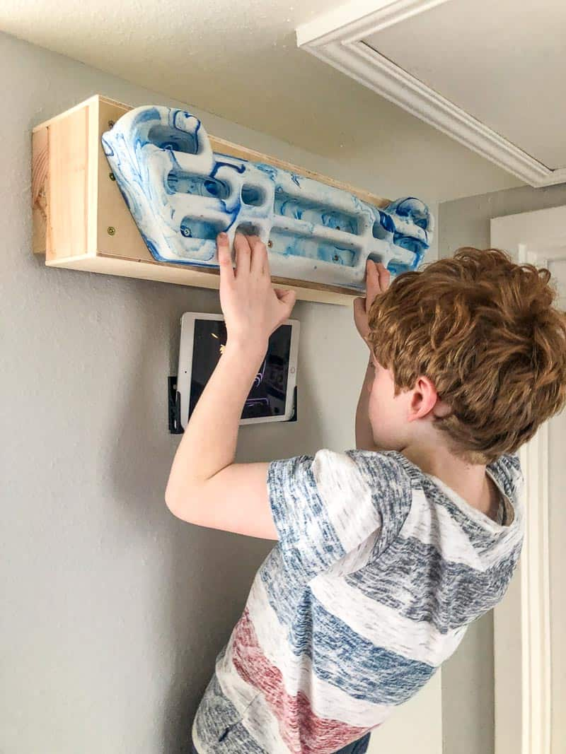 kid using hangboard while watching ipad