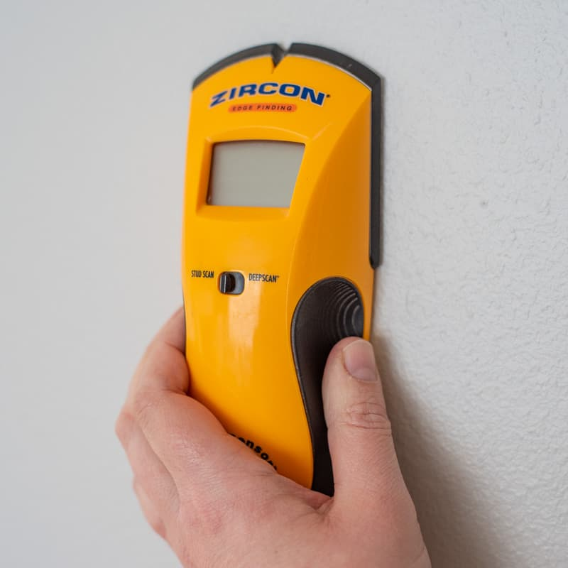 holding electronic stud finder to the wall in the off position