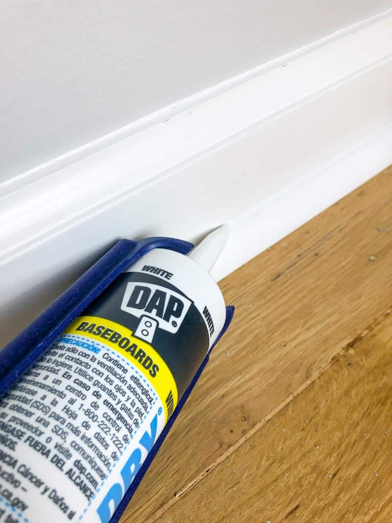 applying caulk to baseboards with a caulk gun