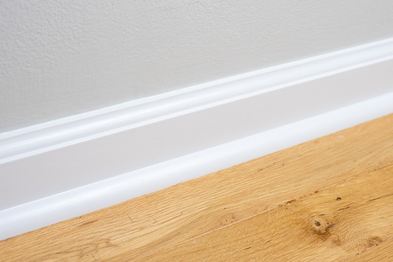 freshly painted baseboards with oak floors