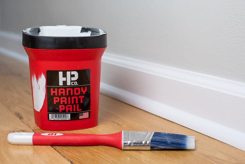 Handy Paint Pail and paint brush next to painted baseboards