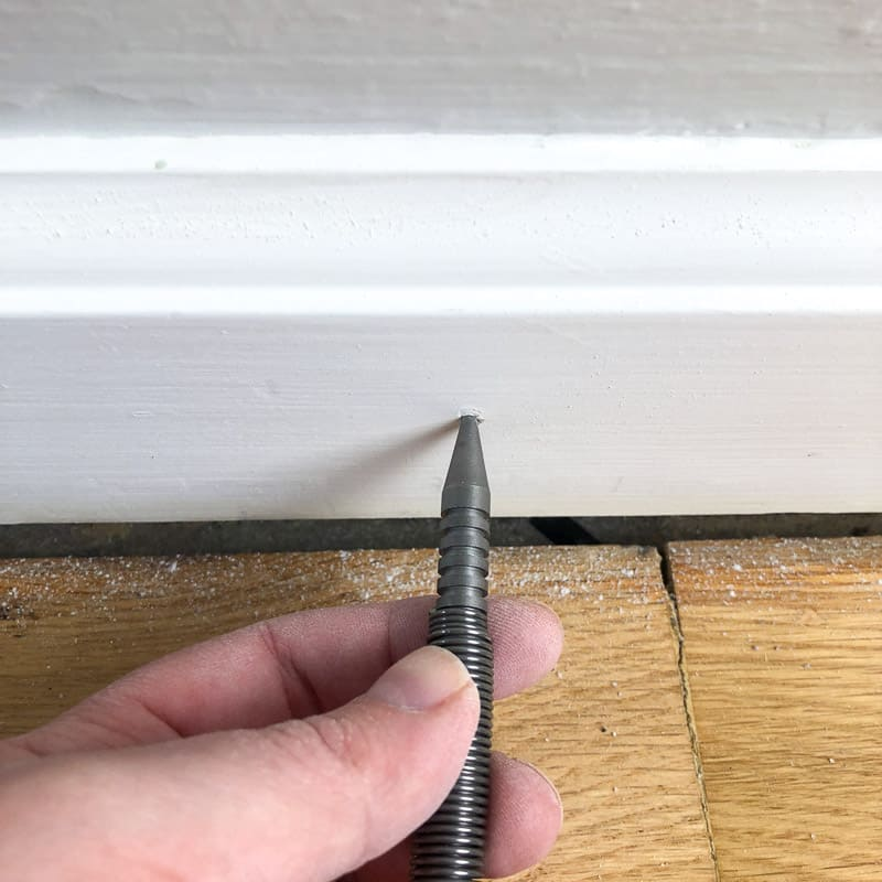 using spring loaded nail set to sink popped nails in baseboards