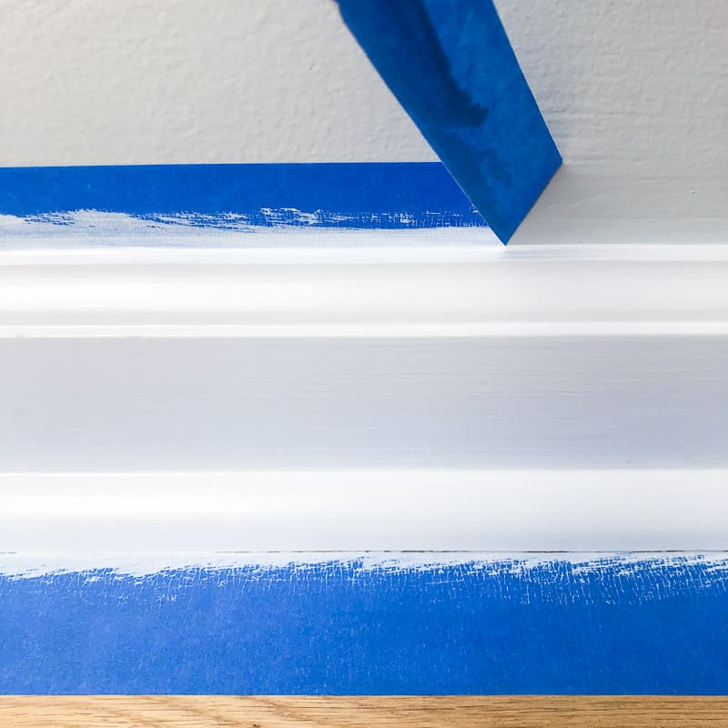 pulling off painter's tape from baseboards