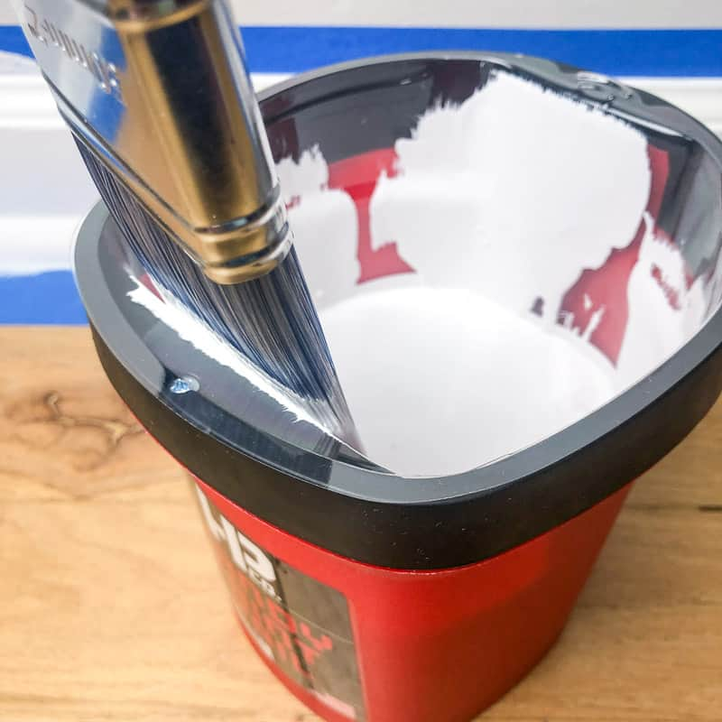 removing excess paint from a paint brush with the edge of the paint pail